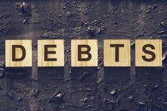 Exprimez les dettes, composées de lettres sur les cubes en bois en construction dans la perspective du vieux fer coloré et fendu  image libre de droits