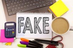 Exprimez les fausses actualités d'écriture dans le bureau avec l'ordinateur portable, marqueur, stylo, papeterie, café Concept d' images libres de droits