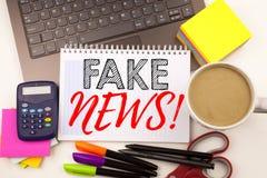 Exprimez les fausses actualités d'écriture dans le bureau avec l'ordinateur portable, marqueur, stylo, papeterie, café Concept d' photos libres de droits