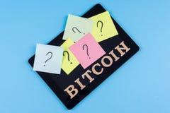 Exprimez les lettres abstraites de bitcoin et remettez en cause les questions sur des autocollants collés au comprimé Image libre de droits