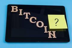 Exprimez les lettres abstraites de bitcoin et remettez en cause les questions sur des autocollants collés au comprimé Photos stock