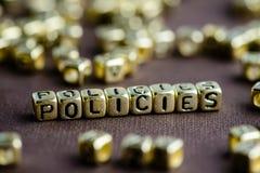 Exprimez les POLITIQUES définies à partir de petites lettres d'or sur le backgr brun Photo stock