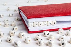 Exprimez les psaumes écrits dans les blocs en bois dans le carnet rouge sur l'OE blanc Photos libres de droits