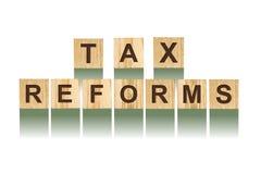Exprimez les réformes fiscales, composées de lettres sur les cubes en bois en construction Fond blanc, affaires d'isolement de co photo stock