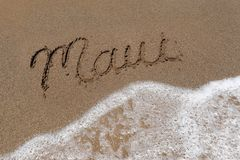 Exprimez Maui écrit dans le sable avec la mousse de mer Photographie stock libre de droits