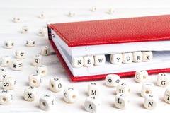 Exprimez New York écrit dans les blocs en bois dans le carnet rouge sur le blanc image libre de droits
