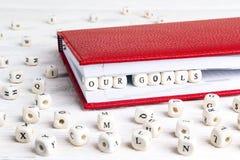 Exprimez nos buts écrits dans les blocs en bois dans le carnet rouge sur le whi images libres de droits