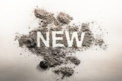 Exprimez nouveau écrit en cendre, la poussière, saleté comme ironie, oxymoron, parado photographie stock libre de droits