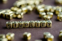Exprimez SIMPLIFY faite à partir de petites lettres d'or sur le backgr brun images libres de droits