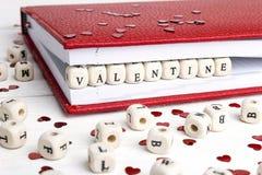 Exprimez Valentine écrit dans les blocs en bois dans un carnet sur le blanc Images libres de droits