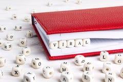 Exprimez viral écrit dans les blocs en bois dans le carnet rouge sur le blanc courtisent image libre de droits