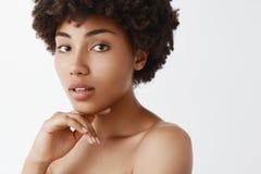 Exprimez votre beaut? naturelle Tir en gros plan de femme ? la peau fonc?e f?minine tendre avec la coiffure boucl?e, touchant le  image stock