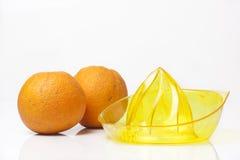 Exprimidor de la fruta cítrica con las naranjas en el fondo blanco Fotos de archivo libres de regalías