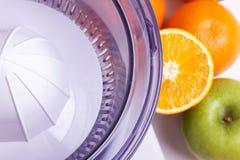 Exprimidor, naranjas y manzana verde Imagenes de archivo