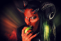 Expulsion. Portrait of a devil with horns holding apple. Devilish temptation. Fantasy. Art project Royalty Free Stock Image