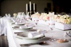 Exquisitamente adornado casandose la tabla con el ramo de rosas Imagenes de archivo