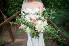 Exquisite bride with a bouquet. Exquisite bride in the boho style rustic with a bouquet Royalty Free Stock Image