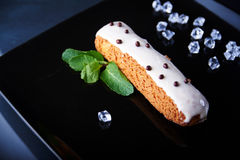 Exquisite cream dessert eclair with fresh mint leaves. On a black plate. Shallow depth of field royalty free stock photos