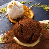 Chocolate fondant with creme anglaise and vanilla ice cream. Exquisite french dessert. Chocolate fondant with creme anglaise and vanilla ice cream, sprinkled royalty free stock images