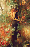 Exquisite girl in a dress with an open back standing in the wood Royalty Free Stock Image