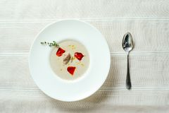 Exquisite mushroom soup puree with pepper, table setting, cozy restaurant serve on a light background.  royalty free stock image
