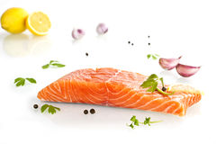 Exquisite salmon steak. Delicious salmon steak with lemon, parsley and garlic isolated on white background stock image