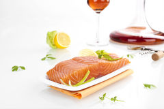 Exquisite salmon steak. Delicious fresh salmon steak arrangement with lemon, parsley and wine isolated on white background royalty free stock photo