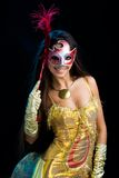 Exquisite woman. Portrate of elegant woman in yellow apparel with venetian mask in hand Stock Image