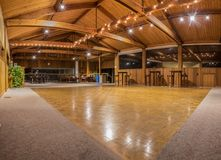 Party lights reflected onto vacant dance floor. Exquisite wood floor and vaulted ceiling interior of dance hall party room with sparkling lights. Pierpont royalty free stock photography