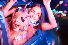 Exspressive女孩看在汽车` s窗口外面并且获得一些乐趣 深色的女孩挥动外面用她的手 免版税库存照片