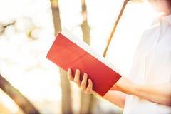 Ext?rieur de fille d'?tudiant tenant un livre rouge au-dessus de fond ensoleill? images stock