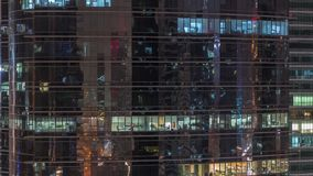 Extérieur de gratte-ciel de bureau pendant fin de soirée avec les lumières intérieures dessus et les personnes travaillant à l'in clips vidéos