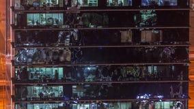 Extérieur de gratte-ciel de bureau pendant fin de soirée avec les lumières intérieures dessus et les personnes travaillant à l'in banque de vidéos