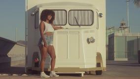 Extérieur de jeune femme de noir de métis, lumière de coucher du soleil d'été, zone de plage de Barcelone banque de vidéos