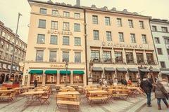 Extérieur de restaurant bavarois historique, de meubles extérieurs en bois et de personnes de marche Photographie stock libre de droits