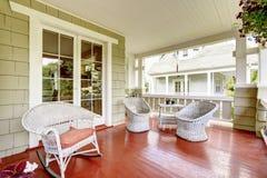 Extasie o patamar com cadeiras de vime e a porta de vidro Fotos de Stock Royalty Free