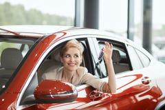 Extatische bestuurdersvrouw die en nieuwe sleutel glimlachen tonen terwijl het zitten in autotoonzaal royalty-vrije stock foto
