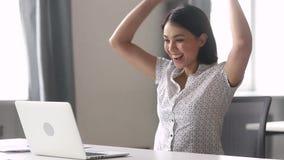 Extatische gelukkige Aziatische bedrijfsvrouwenwinnaar die laptop computer bekijken stock video