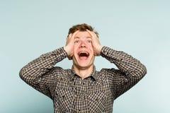 Extatische gelukkige opgewekte mens die hoofdemotie clutching royalty-vrije stock foto