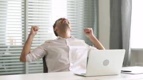 Extatische zakenmanwinnaar die die laptop gevoel gebruiken door online winst wordt opgewekt stock videobeelden