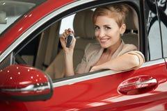 Extatisk chaufförkvinna som ler och visar ny tangent, medan sitta i bilvisningslokal fotografering för bildbyråer