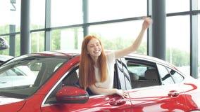 Extatisk chaufförkvinna som ler och visar ny tangent, medan sitta i bilvisningslokal stock video