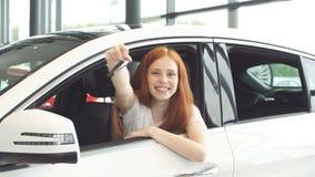 Extatisk chaufförkvinna som ler och visar ny tangent, medan sitta i bilvisningslokal lager videofilmer