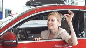 Extatisk chaufförkvinna som ler och visar ny tangent, medan sitta i bilvisningslokal arkivfilmer