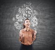 Extatisk kvinna nära en svart tavla med dollartecken arkivbild