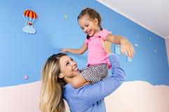 Extatisk lycklig moder och spela för dotter fotografering för bildbyråer