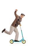 Extatisk pensionär som rider en sparkcykel och gör en gest med hans hand Fotografering för Bildbyråer