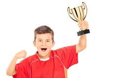 Extatisk pojke som rymmer en guld- kopp Arkivbild