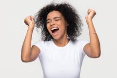 Extatisk ung afrikansk amerikankvinna som skriker med glädje som firar seger arkivfoton