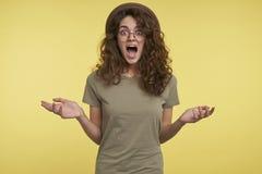 Extatisk ung kvinnlig som isoleras över gul bakgrund arkivfoton